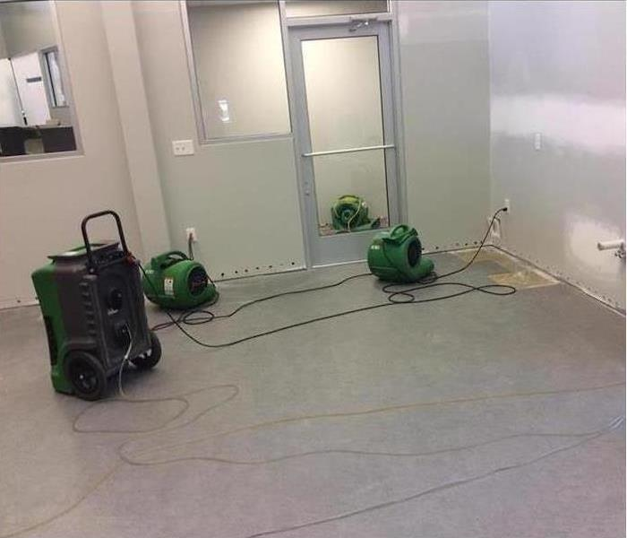 Three air movers and dehumidifier placed on commercial building that has been affected by flooded waters